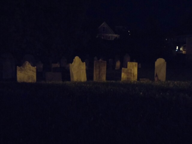 I photographed a cemetery at night. The old headstones have a sepia look; darkness drenches everything else except for some indistinct lights and a barely-visible house in the background.