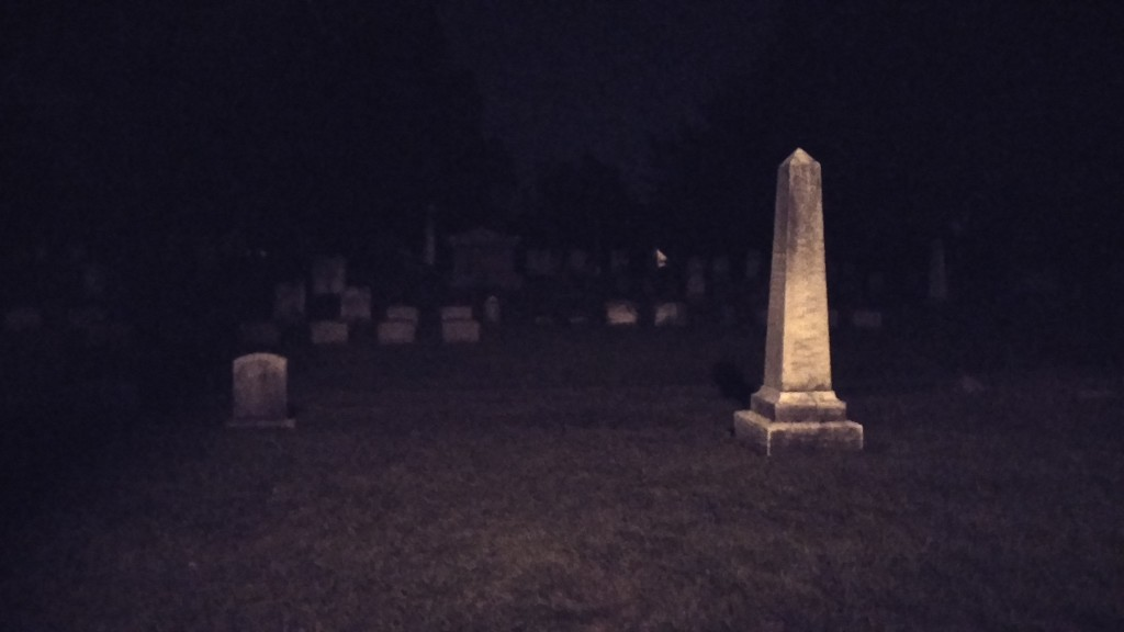 Behold a cemetery at night. While the darkness half hides the other gravestones, a dirty white-ish obelisk stands out clearly.