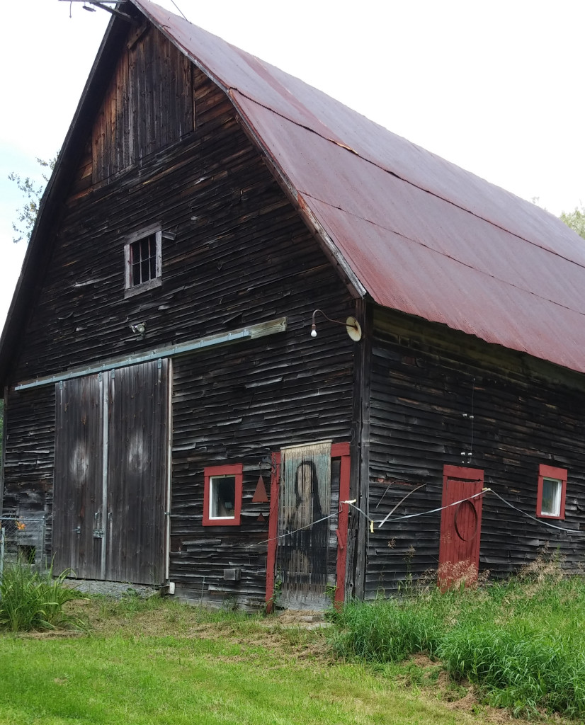 I photographed a dark-colored old barn with some strange features. Over what looks like a boarded-up door hangs a curtain of strips, painted to resemble the Mona Lisa but lacking all detail — most notably, lacking a face. The nearby double doors each sport a blurred white spot, suggesting a pair of eyes.