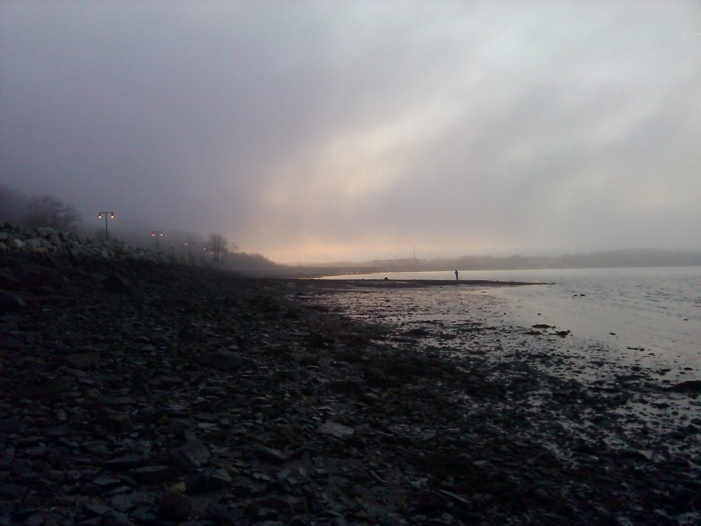 I photographed a black, rocky beach given a supernatural look by a looming shroud of fog and a dim line of street lights receding into the distance.