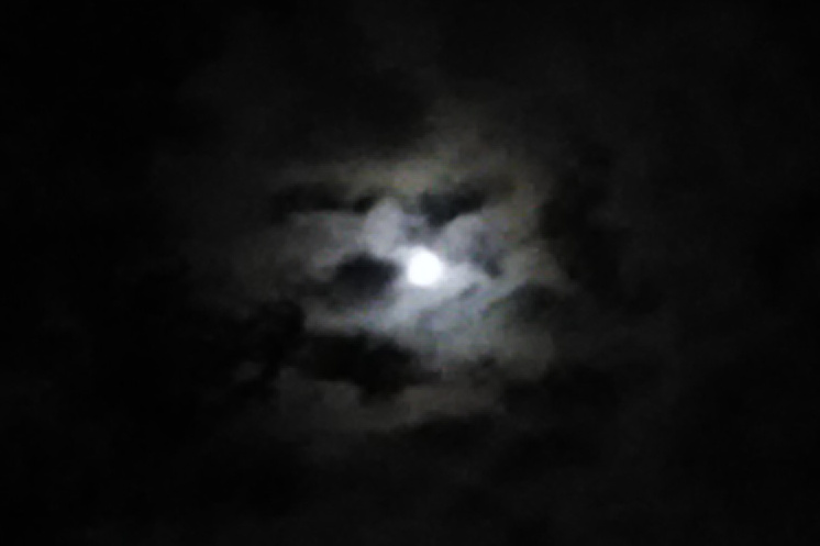 Small dark clouds over a moonlit opening in the night sky form a face.