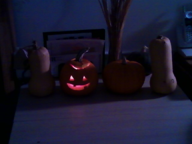 A little lit jack-o'-lantern and a little uncarved pumpkin between 2 butternut squashes on a table in a dim room.
